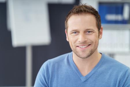 affaires Handsome avec un sourire amical regarder la caméra comme il est assis dans le bureau dans une chemise décontractée