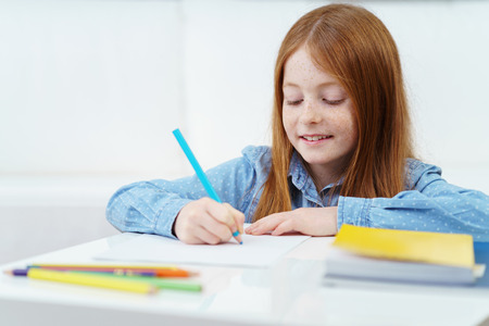 schoolwork: Pretty creative little girl drawing with a colored pencil as she does her schoolwork at home smiling with pleasure as she amuses herself