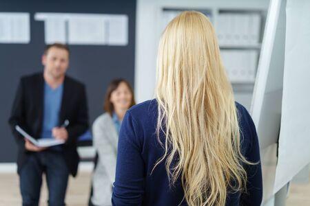 comunicarse: Vista desde la parte trasera de una mujer de negocios rubia con el pelo largo suelto caminando en la oficina acercarse dos compañeros de trabajo