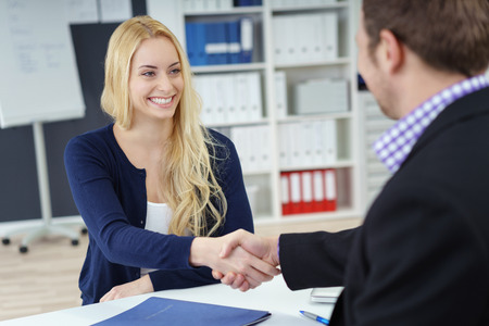 deal in: Businessman and woman shaking hands across an office desk as they seal a deal, in partnership, congratulations or in welcome, focus to attractive young woman Stock Photo