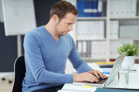 entering information: Businessman entering data on his laptop computer as he types in the information with an absorbed expression, side view Stock Photo