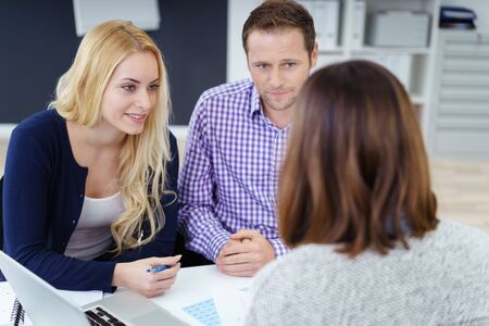 advisers: Young couple in a meeting with an adviser or business colleague listening intently to what she is saying , view over the advisers shoulder of the young man and woman