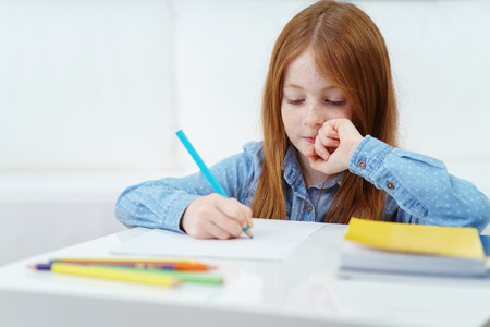 niña pensando: Niña linda reflexivo sentado en una mesa en su casa haciendo la tarea para la escuela mientras se escribe o dibuja con un lápiz de color