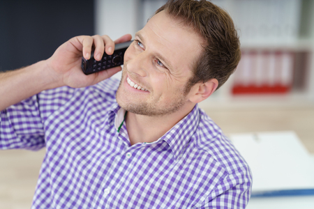 broadly: Businessman taking a call in the office on a telephone smiling broadly with pleasure as he listens to the conversation, close up head and shoulders Stock Photo