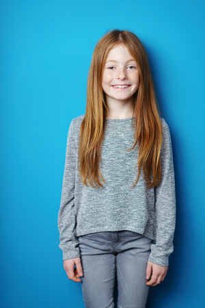brunette girl: Young redhead girl with an engaging smile standing in front of turquoise blue background with copy space