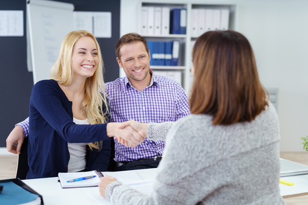advice: Happy couple shaking hands with a female business broker or investment adviser as they attend a meeting in her office