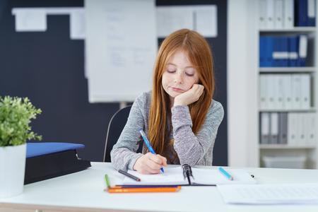 gente sentada: Colegiala joven que hace su preparación sentarse en una mesa de escribir notas en un bloc de notas con una expresión de aburrimiento