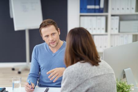 Young Business-Team oder eine Partnerschaft, eine ernsthafte Diskussion an einem Tisch im Büro mit Fokus auf ein ernster stattlicher junger Mann,