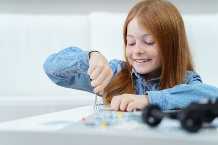 Pretty little roodharige meisje zitten aan een tafel thuis werken met een schroevendraaier met een stralende glimlach
