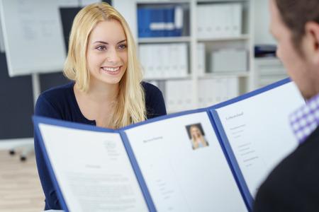 Привлекательный молодой предприниматель в собеседовании с корпоративным менеджером по персоналу, который читает ее резюме в синей папке, через фокус плечо к молодому заявителю Фото со стока