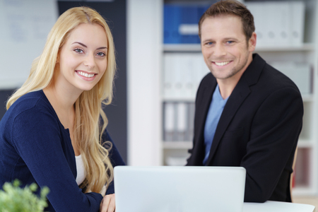 businessman in office: Successful young business couple working together on a self-employed business posing at a desk in their office smiling at the camera