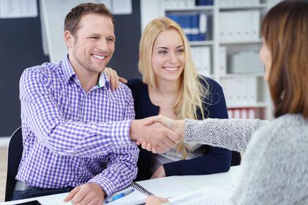 Lachende blij aantrekkelijke jonge paar handen schudden met een zakelijke makelaar of adviseur als ze zitten met haar in het kantoor in een vergadering, uitzicht over de adviseurs schouder