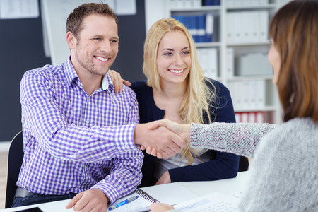 advisers: Smiling pleased attractive young couple shaking hands with a business broker or adviser as they sit with her in the office in a meeting, view over the advisers shoulder