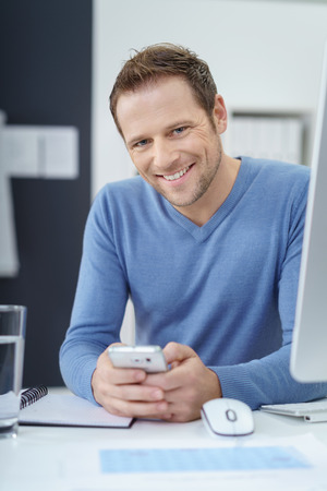 one young man: Handsome businessman sitting at his desk in the office holding a mobile phone smiling at the camera