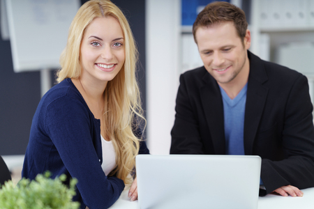 co operation: Business partners working together at a laptop computer in the office with focus to a smiling friendly young blond woman alongside a handsome man Stock Photo