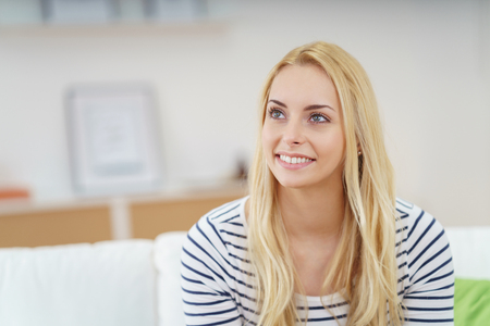 attractive woman: Gorgeous young blond woman with a vivacious smile sitting at home on the sofa reminiscing happy memories