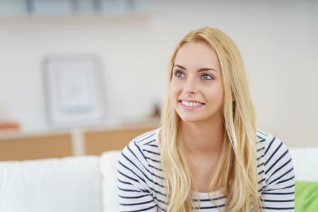mujer sola: mujer joven rubia con una sonrisa vivaz sentado en su casa en el sofá recordando recuerdos felices