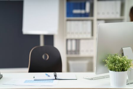 unattended: Unattended workstation in an office with a chair, paperwork and potted plant Stock Photo