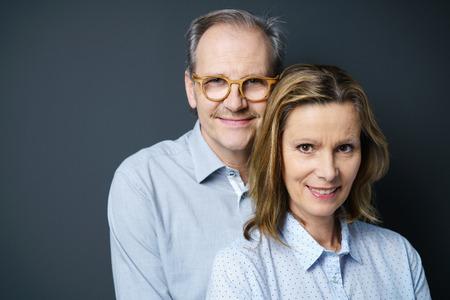 casados: retrato de una pareja de mediana edad de pie muy juntos