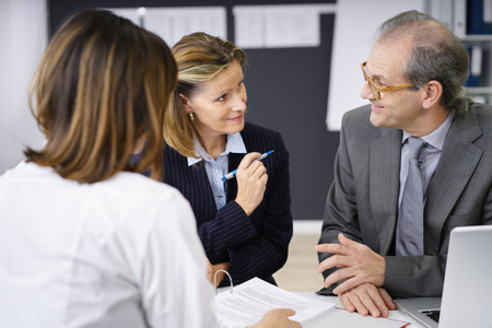 Middle-aged couple having a serious discussion together as they attend a meeting with a female investment adviser Stock Photo