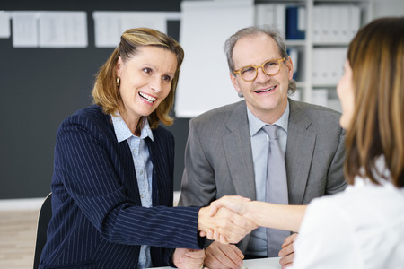 financial planning married: Two business women shaking hands at the end of a meeting between an investment broker and a middle-aged couple planning their retirement