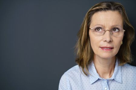 copy space: middle-aged woman with a pensive facial expression standing against grey background with copy-space