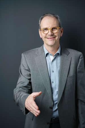 conclude: Smiling middle-aged businessman in glasses offering to shake hands to conclude a deal, in welcome or to seal a partnership, against a dark background Stock Photo