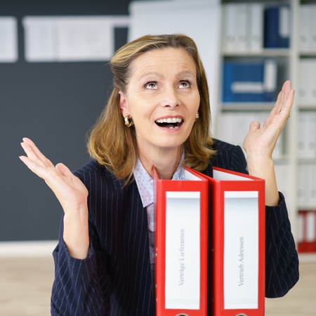 exclaiming: Businesswoman exclaiming in amazement gesturing with her hands above two office binders as she raises her eyes with her mouth open Stock Photo