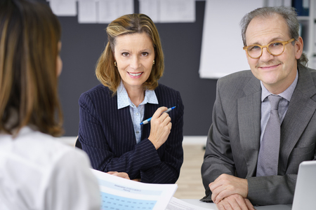 senior female: Smiling confident middle-aged couple having a meeting with a female adviser or broker as they plan for their retirement