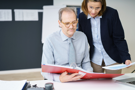 Office women: senior partners in the office checking papers in a red folder