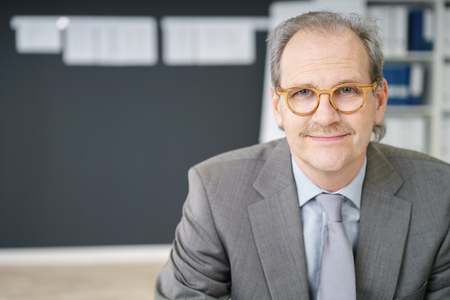 smiling businessman: middle-aged businessman wearing eye-glasses looking at the camera Stock Photo