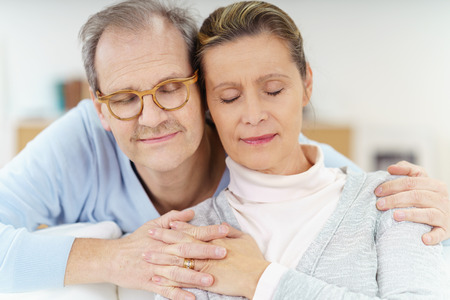 close together: happy middle-aged couple holding heads close together with eyes closed