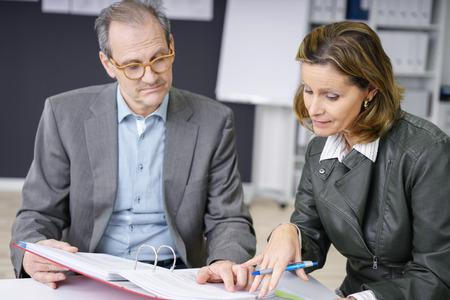 profesor: equipo de gestión de documentos de discusión, ya que están sentados en el escritorio en una oficina moderna