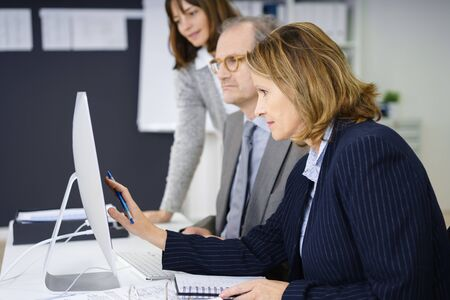 working woman: motivated business woman working with two colleagues Stock Photo