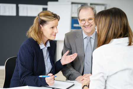 financial planning married: Three diverse business colleagues sitting round an office table having an animated discussion with focus to an attractive middle aged woman Stock Photo