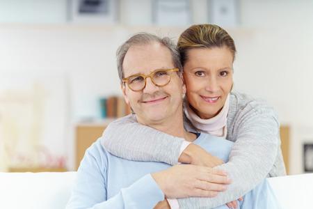 glimlachend paar in hun vijftiger jaren ontspannen en omarmen thuis