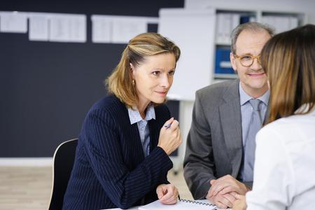 echtpaar van middelbare leeftijd in een ontmoeting met een vrouwelijke agent of makelaar luistert aandachtig naar haar met een glimlach, over de schouder view