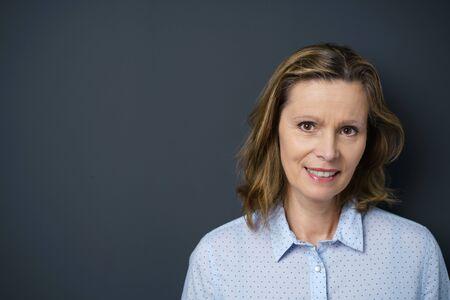 ritratto di una donna di mezza età sorridente che indossa una camicetta blu