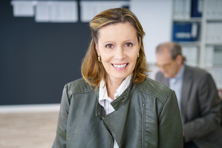 management team: confident middle-aged businesswoman in the office with a colleague sitting in background Stock Photo