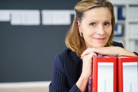 Friendly thoughtful middle-aged businesswoman resting her chin on office binders smiling at the camera, close up view with copy space Stock Photo