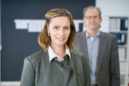 coworker: experienced successful businesswoman with her co-worker standing in background Stock Photo