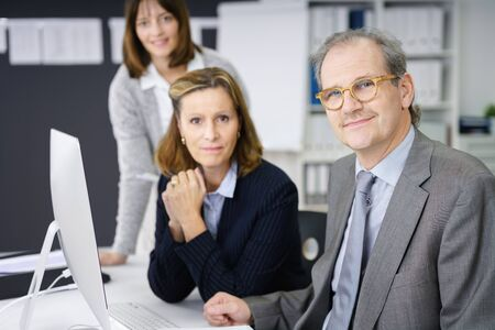 manager team: Successful middle-aged business team working together around a desktop computer with focus to an attractive manageress in the centre Stock Photo