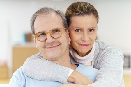 romantic: Smiling contented middle-aged man wearing glasses being hugged from behind by his wife as they relax together on the sofa at home Stock Photo