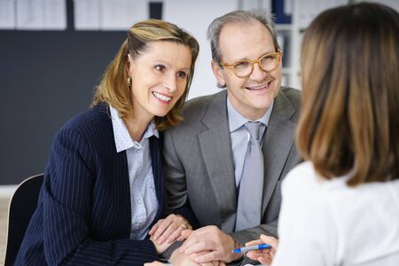financial planning married: Smiling middle-aged couple in a meeting with an investment adviser planning for their future retirement, over the shoulder view