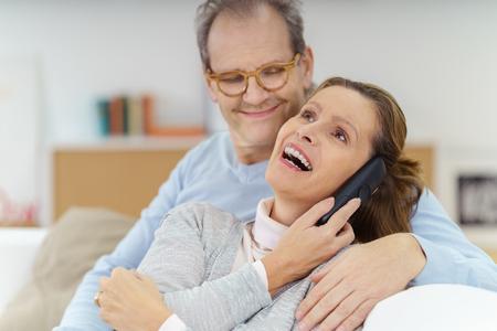 hablando por telefono: La mujer atractiva riendo con alegría mientras se toma una llamada en su teléfono móvil observó con afecto por su marido Foto de archivo