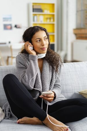 Full Length of Young Woman Relaxing at Home with Cell Phone Music Player and Headphones - Woman Curled Up on Sofa with Personal Music Player and Enjoying Relaxing Day at Home Stock Photo