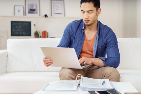 Junge asiatische männliche Studentin studiert zu Hause sitzen auf dem Sofa arbeiten auf seinem Laptop-Computer mit Papierkram vor ihm