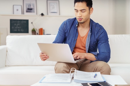 Young Asian male student studying at home sitting on the sofa working on his laptop computer with paperwork in front of him