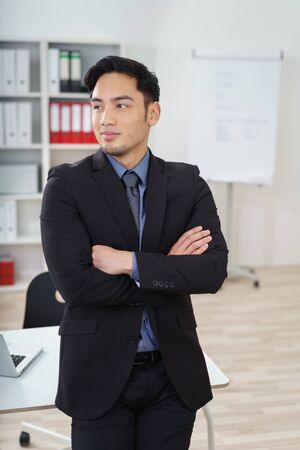 asian guy: Confident Asian businessman watching a colleague ashe stands in his formal suit with crossed arms looking to the side with a smile