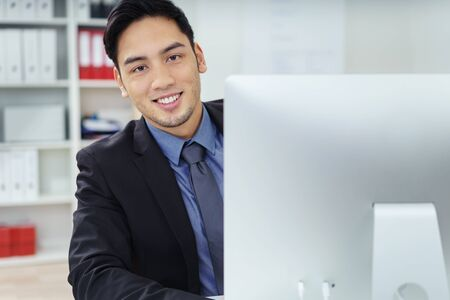 apprenticeship employee: Friendly Asian businessman looking around the side of his desktop monitor to smile at the camera a he sits at his desk in the office